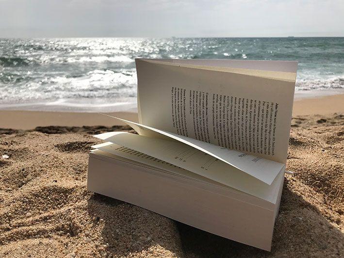universo paralelo con libro en playa